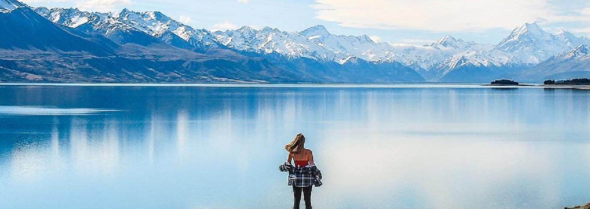 Woman looking out on New Zealand lake