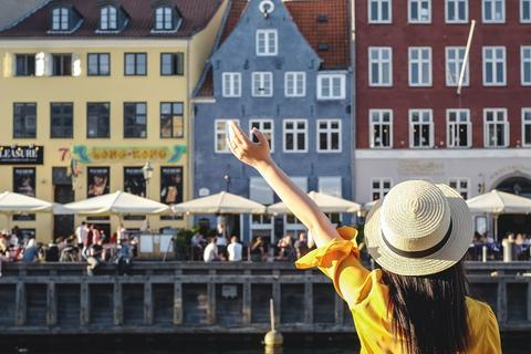 Woman waving in front of European canal