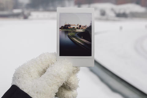 A girl holding a polaroid picture in Krakow in wintertime.
