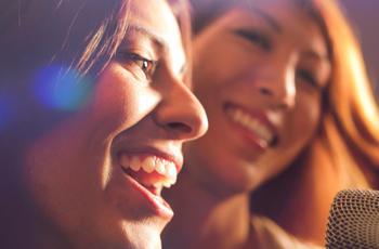 Two young women singing karoke