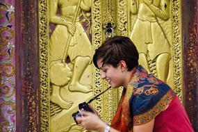 Woman taking a photo of a cat in Asia. Photo: Contiki.