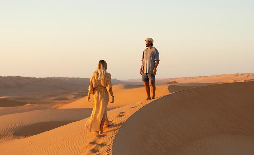 Couple walking on sand dunes